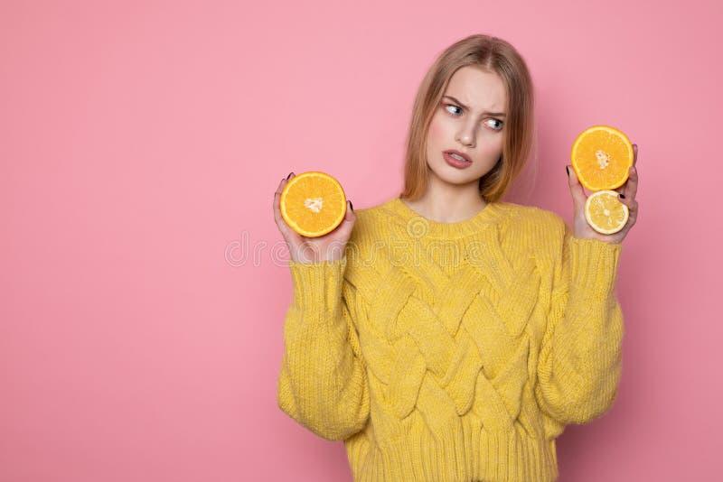 有金发的,佩带的黄色毛线衣生气震惊年轻女人 免版税库存照片