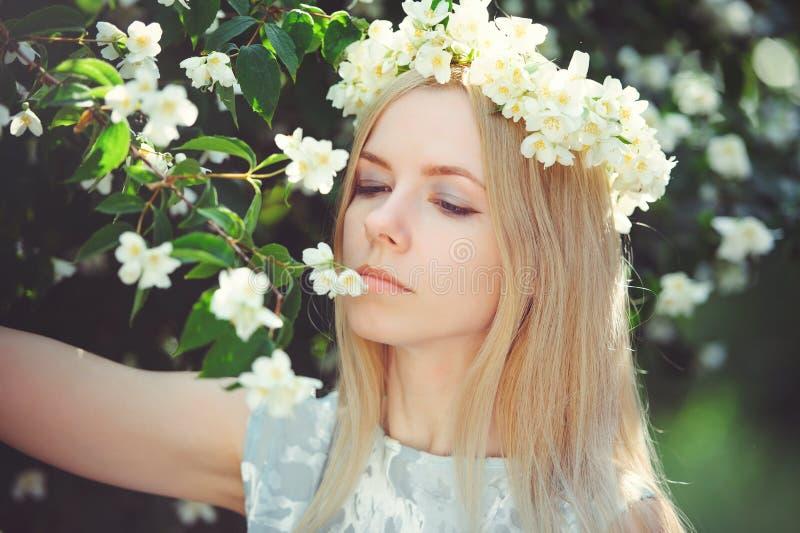 有金发碧眼的女人的可爱的谦虚女孩有茉莉花花的在顶头长的头发和自然构成缠绕在白色礼服户外 库存图片