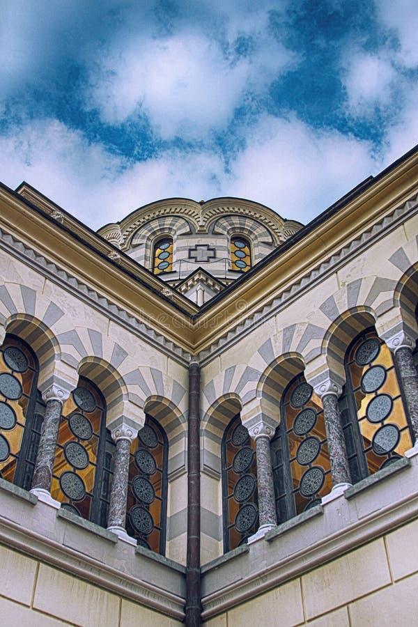 有金圆屋顶的美丽的白色石教会,与云彩的天空蔚蓝 库存图片