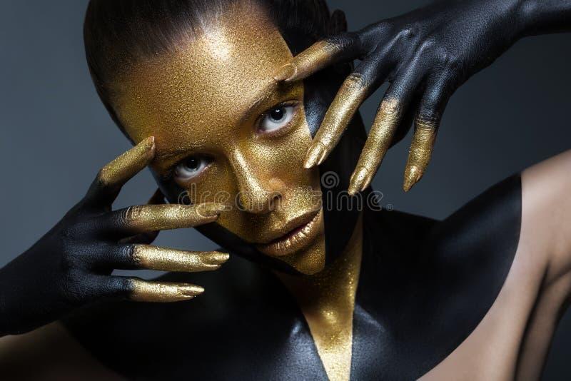 有金子和黑油漆的女孩在她的面孔和身体 库存图片