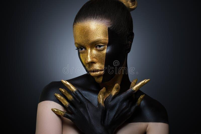 有金子和黑油漆的美女在她的面孔和身体 与创造性的构成的女性画象 方式 免版税图库摄影