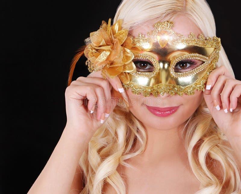 有金子狂欢节面具的白肤金发的女孩在黑背景。化妆舞会 图库摄影