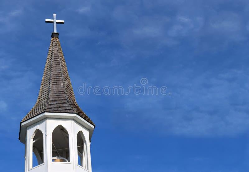 有金属十字架的教会屋顶在与蓬松云彩的顶面和白色钟楼 免版税库存照片