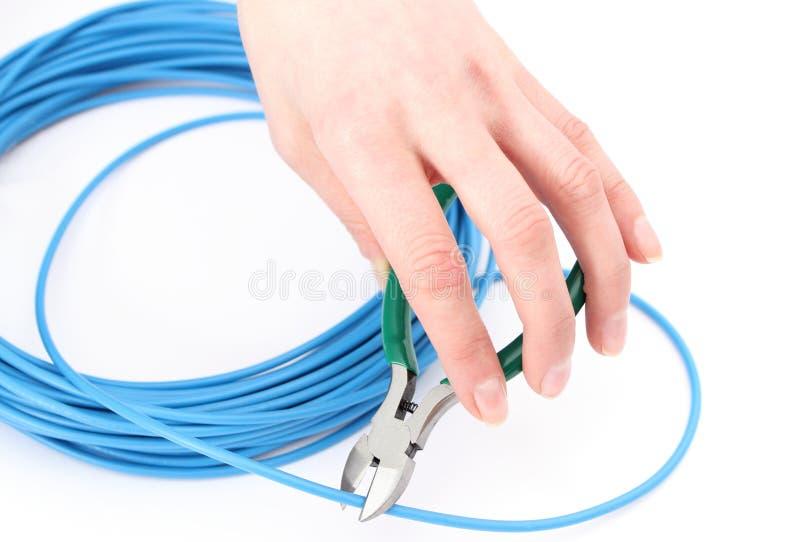 有金属少年的手切开缆绳 库存照片