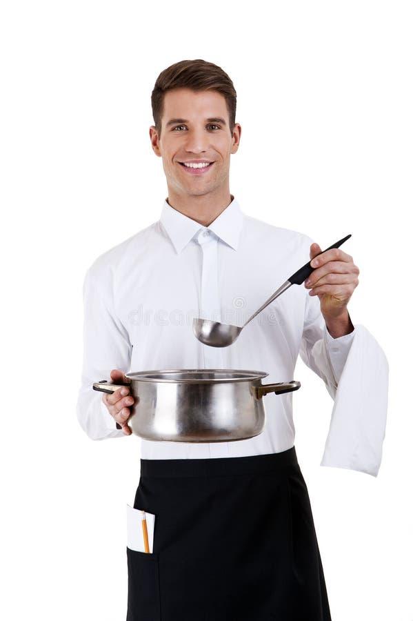 有金属平底锅罐的微笑的年轻侍者 库存图片