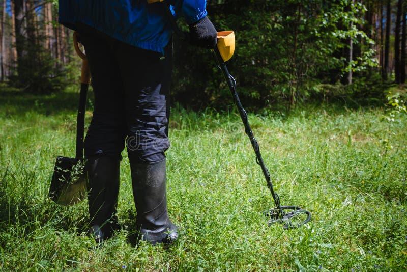 有金属探测器的一个人在森林 库存图片
