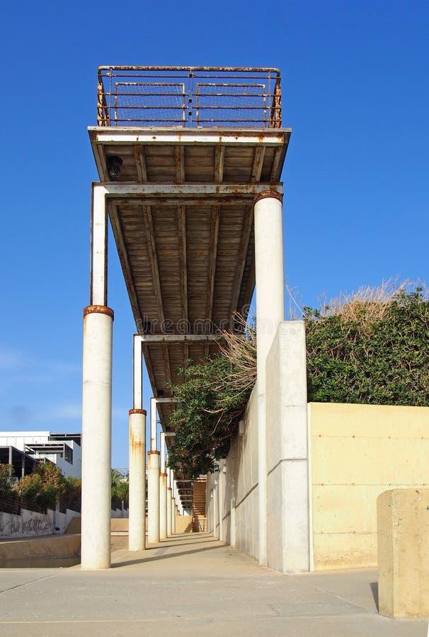 有金属栏杆和具体专栏的老生锈的被放弃的码头在与一被日光照射了天空蔚蓝的paphos塞浦路斯 免版税库存图片