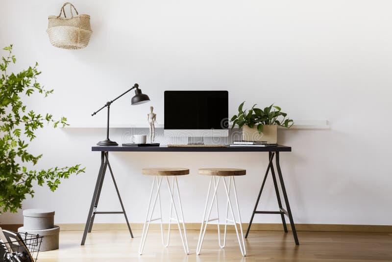 有金属灯、新鲜的植物和大模型显示器的黑书桌安置的两把簪子凳子在白色客厅interio真正的照片  库存图片