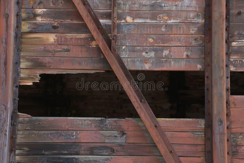 有金属纹理的残破的棕色木墙壁。 免版税图库摄影