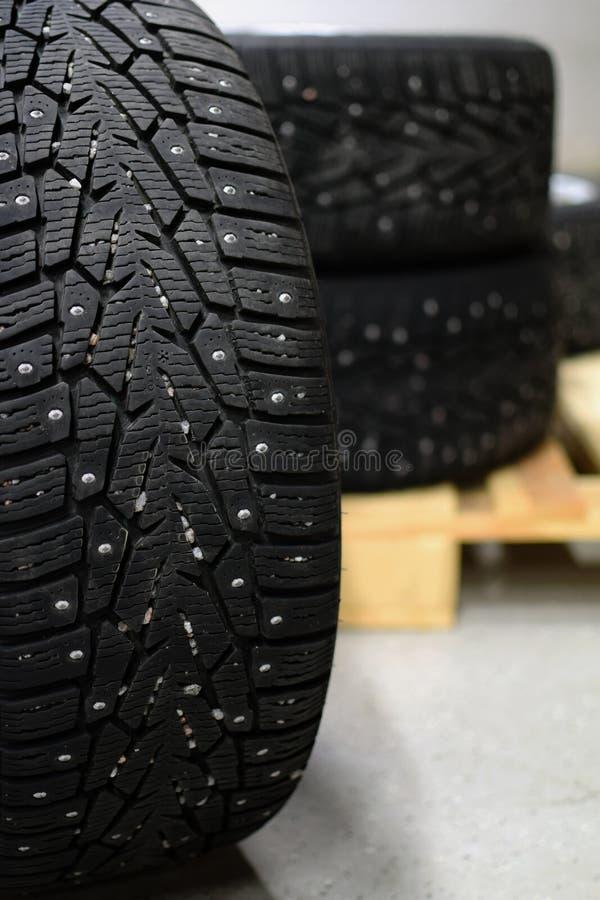 有金属螺柱的防滑轮胎在车库 库存图片