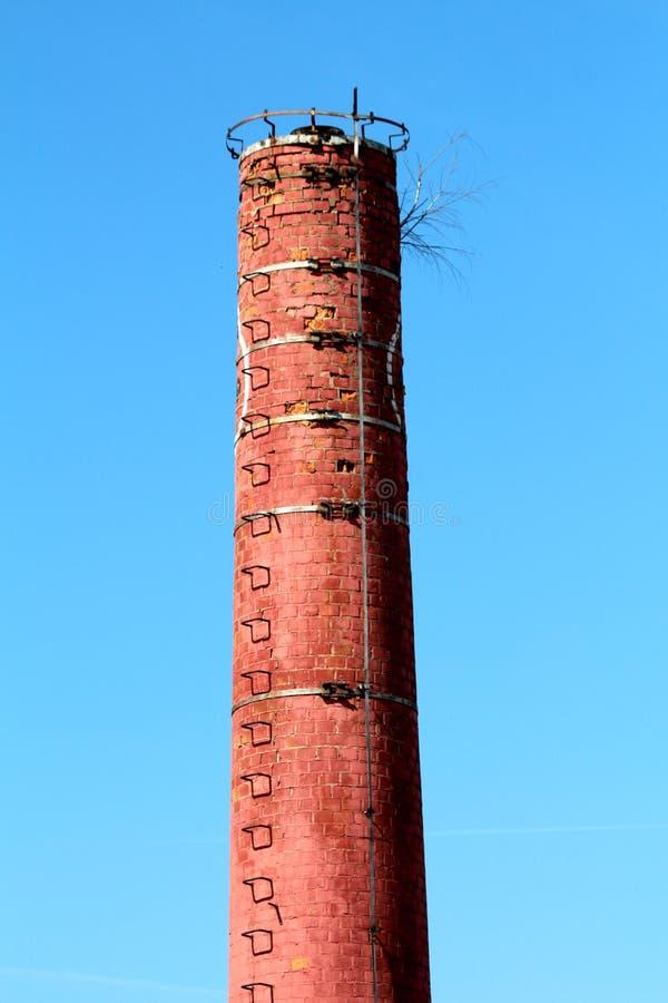 有金属避雷针的高红砖工业没有安全导线的烟囱和步在被放弃的工业体系 库存照片