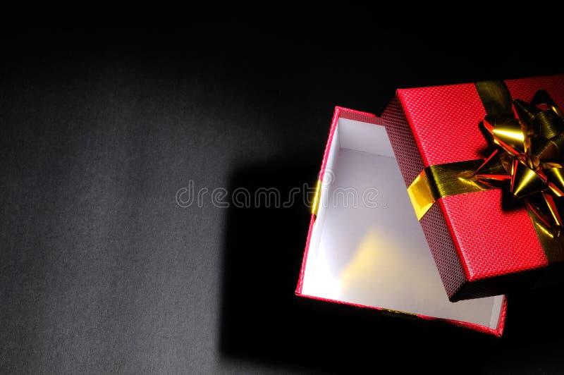 有金弓昏暗的上面的空的开放红色礼物盒 库存图片