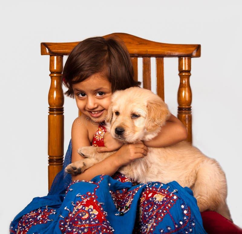 有金毛猎犬小狗的逗人喜爱的女孩 免版税库存照片