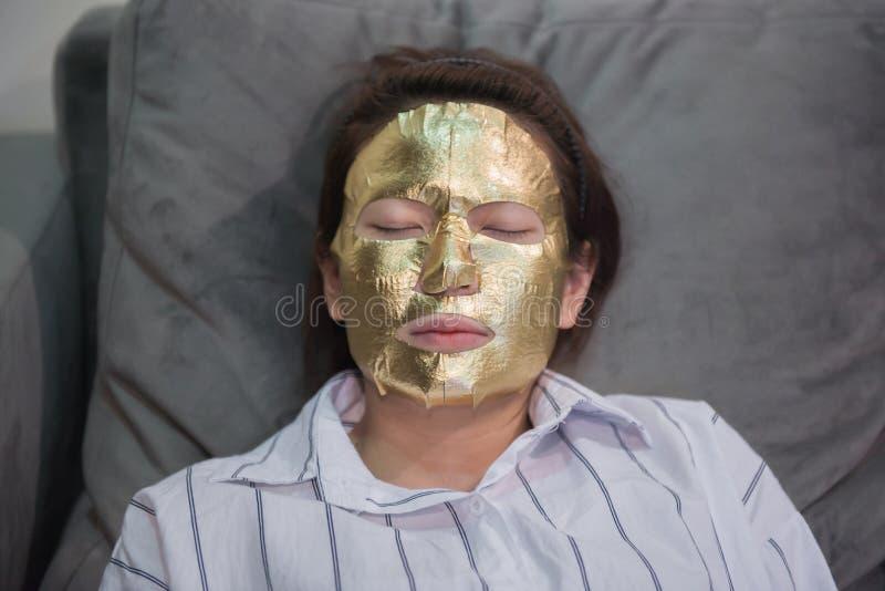 有金脸面护理面具的女孩 图库摄影