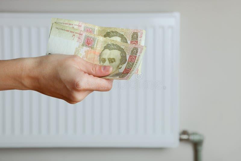 有金钱和热电池的手 免版税库存图片