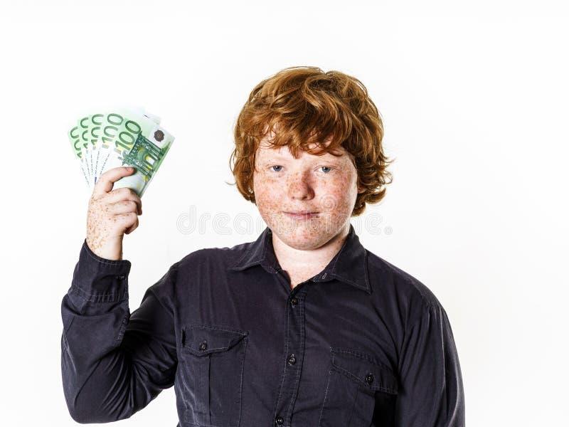 有金钱的愉快的红发男孩 库存图片