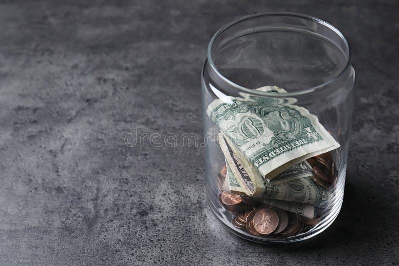 有金钱的捐赠瓶子在灰色背景 免版税库存照片
