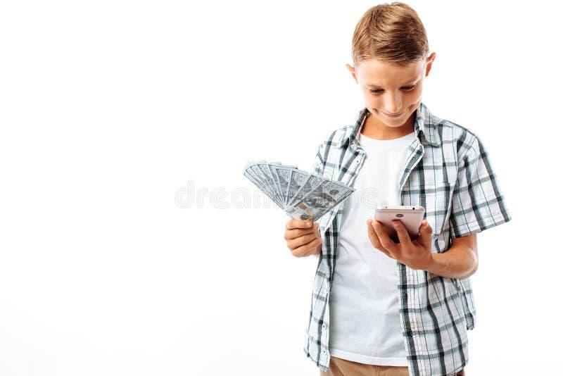 有金钱的英俊的青少年的人在他的手上,在电话,拿着美元的快乐的人写,在白色背景的演播室 免版税库存图片