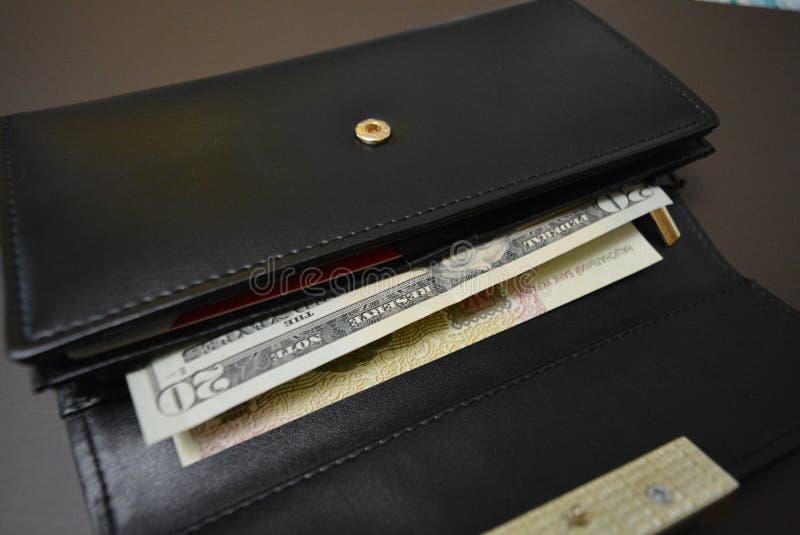 有金钱的黑皮革钱包在它在棕色表面无光泽的背景 钞票20二十美国美元和100一百Ukrain 免版税库存图片