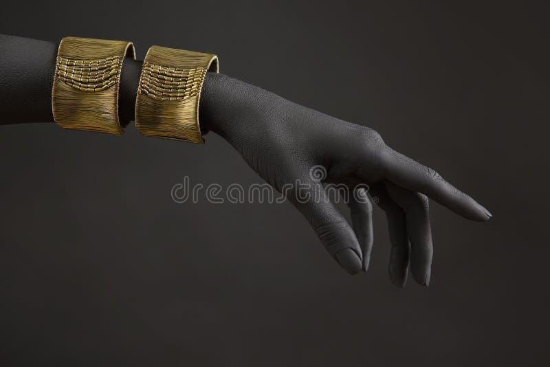 有金首饰的黑人妇女的手 在手上的东方镯子 金首饰和豪华 库存图片
