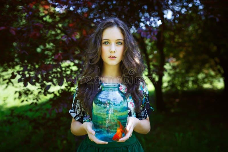 有金鱼的年轻美丽的女孩 免版税库存图片