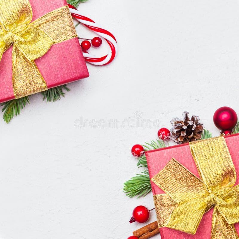 有金黄丝带和弓的圣诞节红色礼物盒在白色背景,舱内甲板与拷贝空间的被放置的顶视图 免版税库存照片
