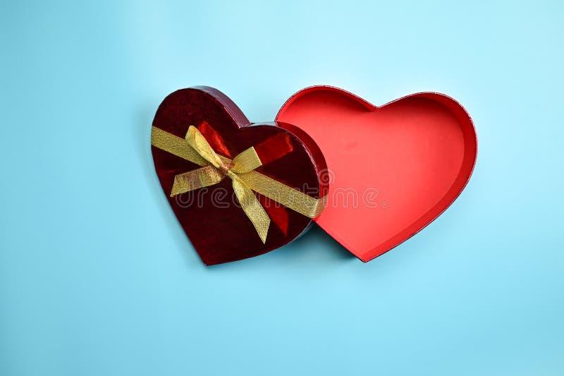 有金黄丝带弓的开放红心形状礼物盒 免版税库存图片