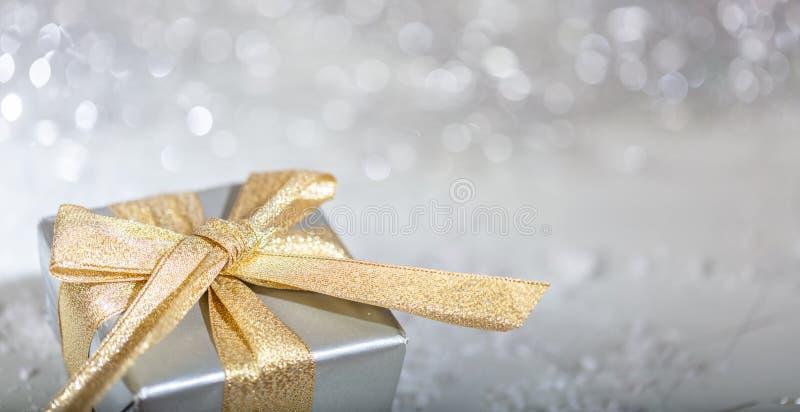 有金黄丝带的圣诞礼物箱子在抽象bokeh光和闪烁背景 免版税库存照片