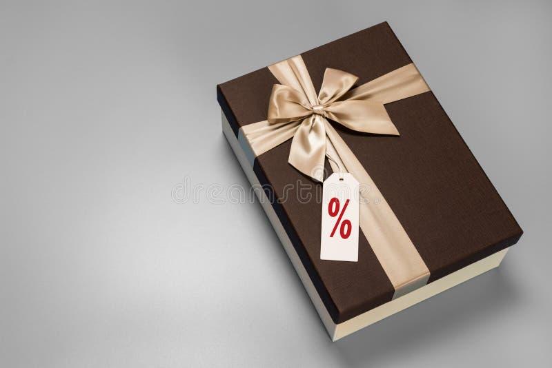 有金黄丝带的布朗箱子和与红色百分比标志的一个标签附属的 库存图片