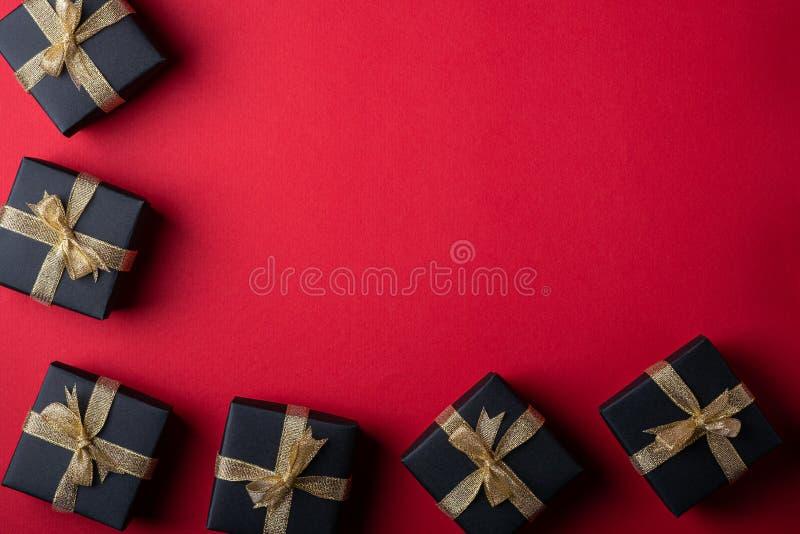 有金黄丝带的黑礼物盒在红色纸框架边界背景,顶视图,平的位置 库存照片