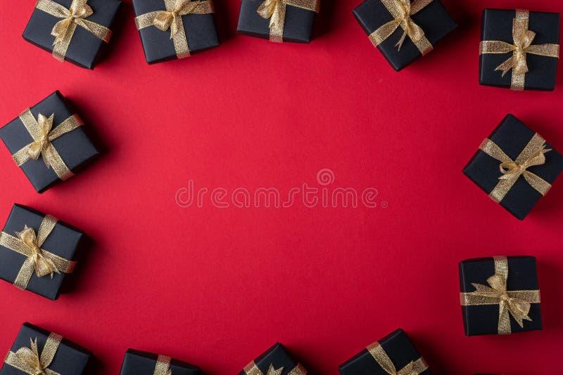 有金黄丝带的黑礼物盒在红色纸框架边界背景,顶视图,平的位置 库存图片