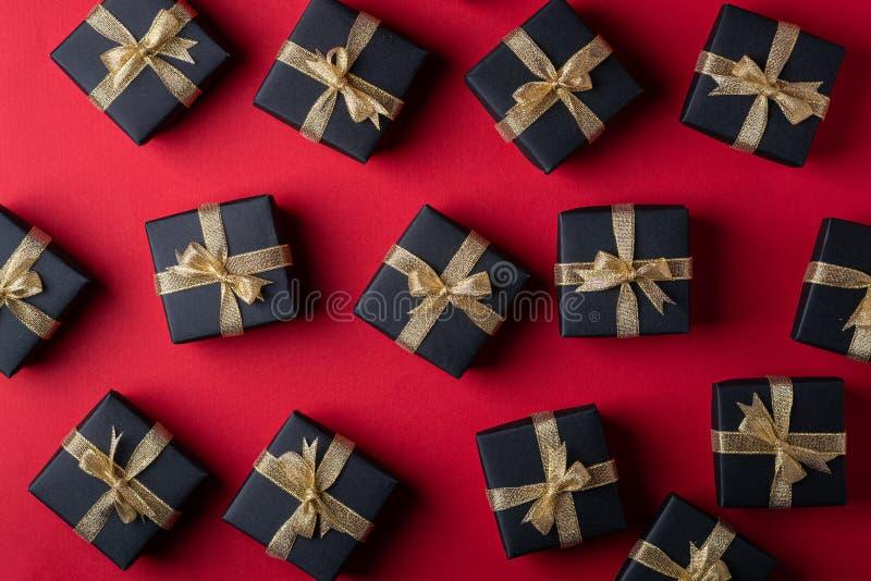 有金黄丝带的黑礼物盒在红色纸背景,样式,纹理,被隔绝的,顶视图 免版税库存图片