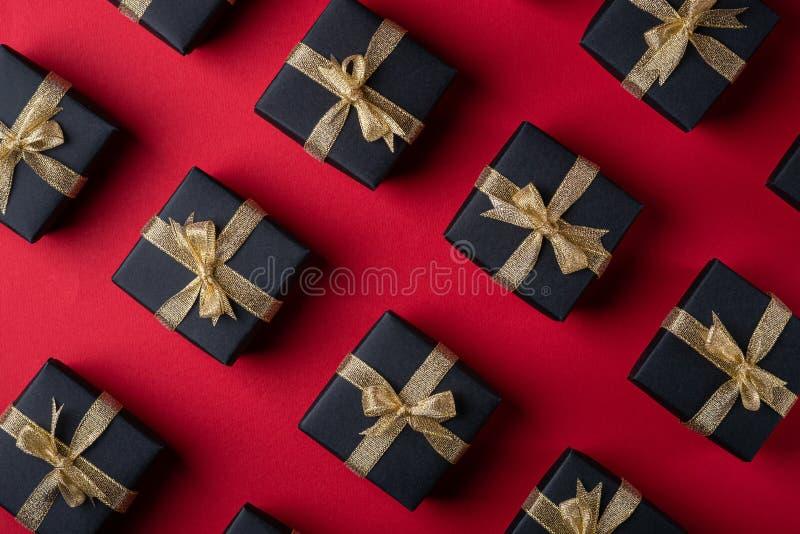 有金黄丝带的黑礼物盒在红色纸背景,样式,纹理,被隔绝的,顶视图 库存照片