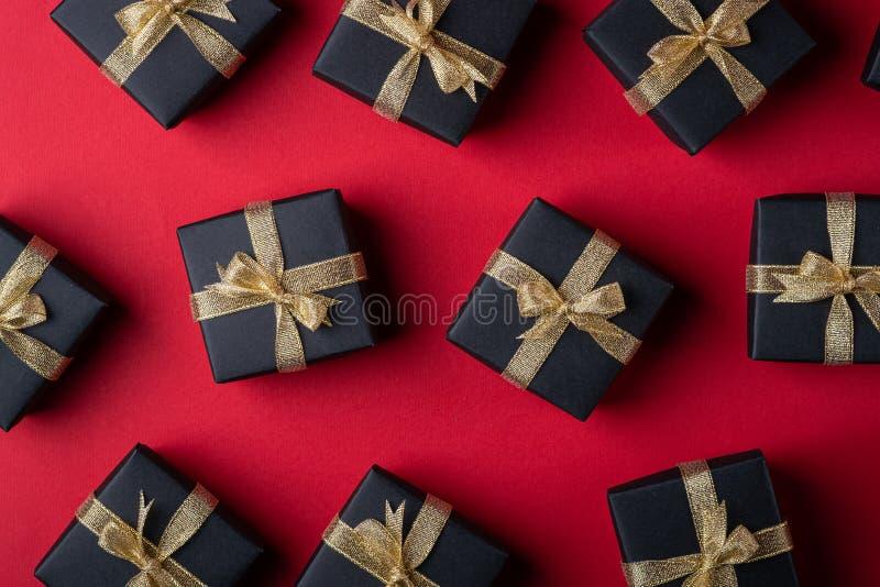 有金黄丝带的黑礼物盒在红色纸背景,样式,纹理,被隔绝的,顶视图 免版税库存照片
