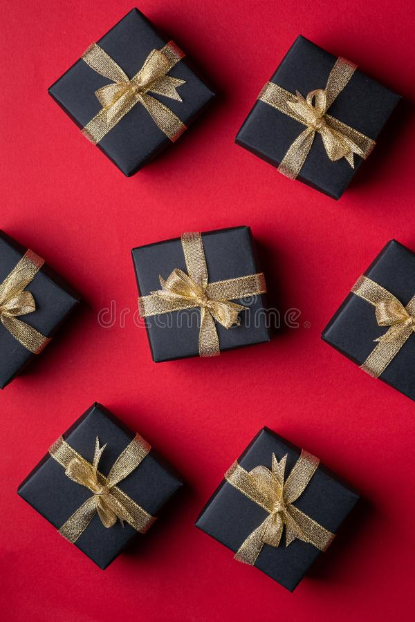 有金黄丝带的黑礼物盒在红色纸背景,样式,纹理,被隔绝的,顶视图 图库摄影