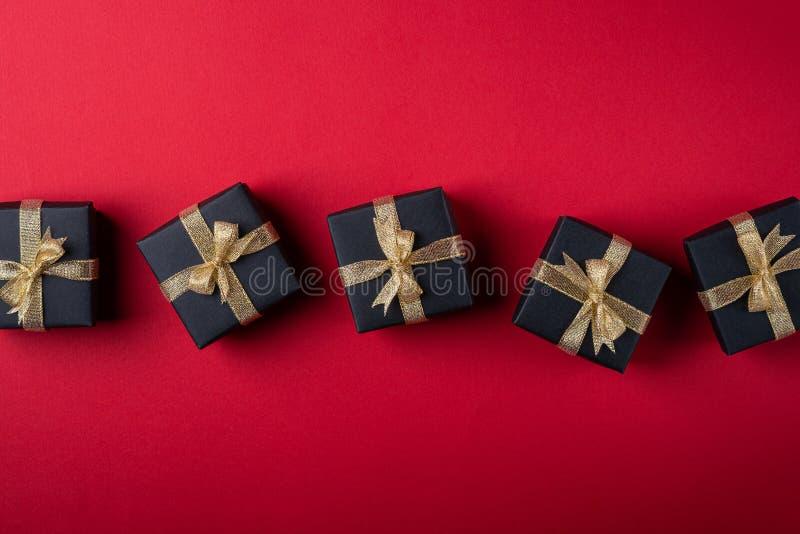 有金黄丝带的黑礼物盒在红色纸背景,纹理,被隔绝的,顶视图的线 免版税库存图片