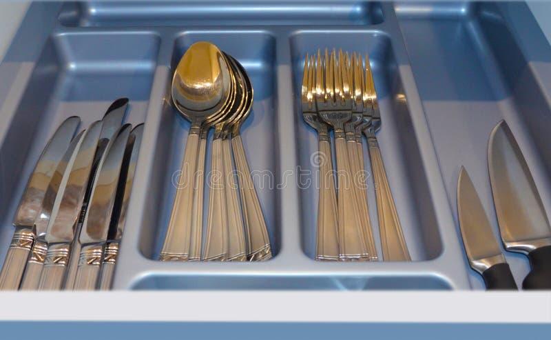有金黄利器的灰色盘子在一个开放厨房抽屉 图象 免版税库存照片