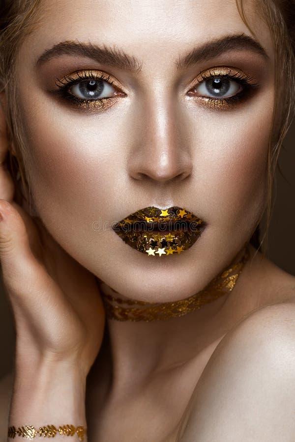 有金黄发光的构成的美丽的在她的嘴唇的女孩和星 秀丽表面 免版税库存照片