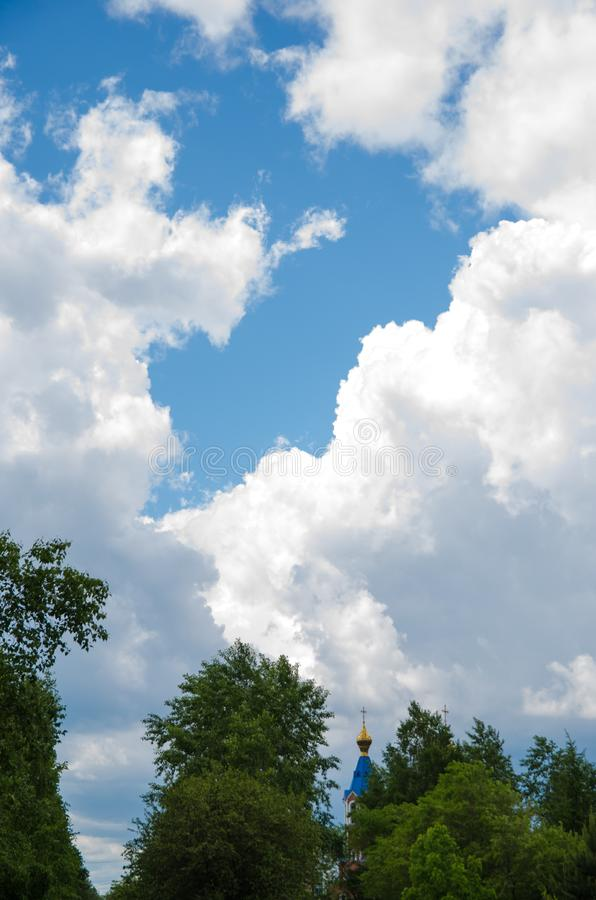 有金黄圆顶的教会和从在远处的一个十字架反对与白色云彩和树的一天空蔚蓝在前景 免版税图库摄影
