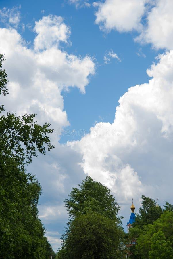 有金黄圆顶的教会和从在远处的一个十字架反对与白色云彩和树的一天空蔚蓝在前景 免版税库存照片