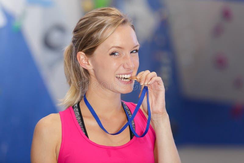 有金黄奖牌的年轻女人在嘴附近 图库摄影