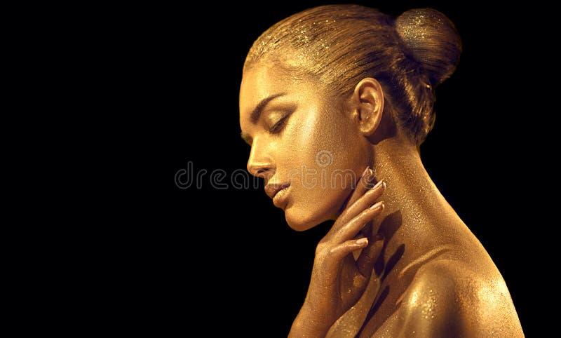 有金黄皮肤的秀丽性感的妇女 时尚艺术画象特写镜头 有发光的金黄专业构成的式样女孩 库存图片