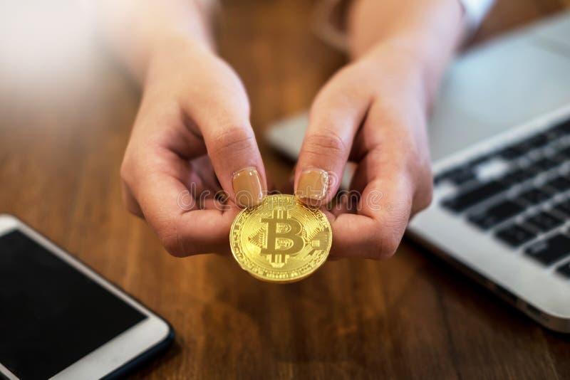 有金黄金属Bitcoin隐藏货币投资symbo的手 免版税库存照片