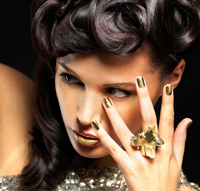 有金黄钉子和方式构成的美丽的妇女 免版税库存照片