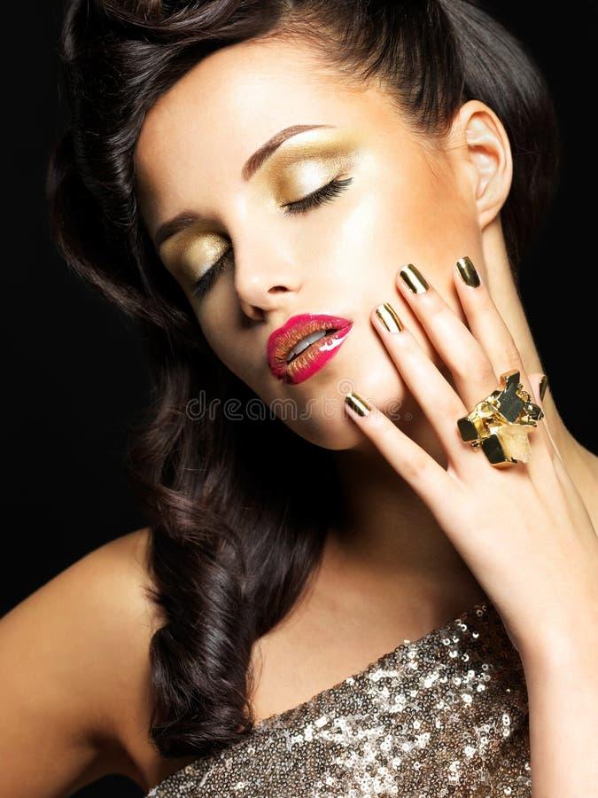 有金黄钉子和样式构成的美丽的妇女 库存图片
