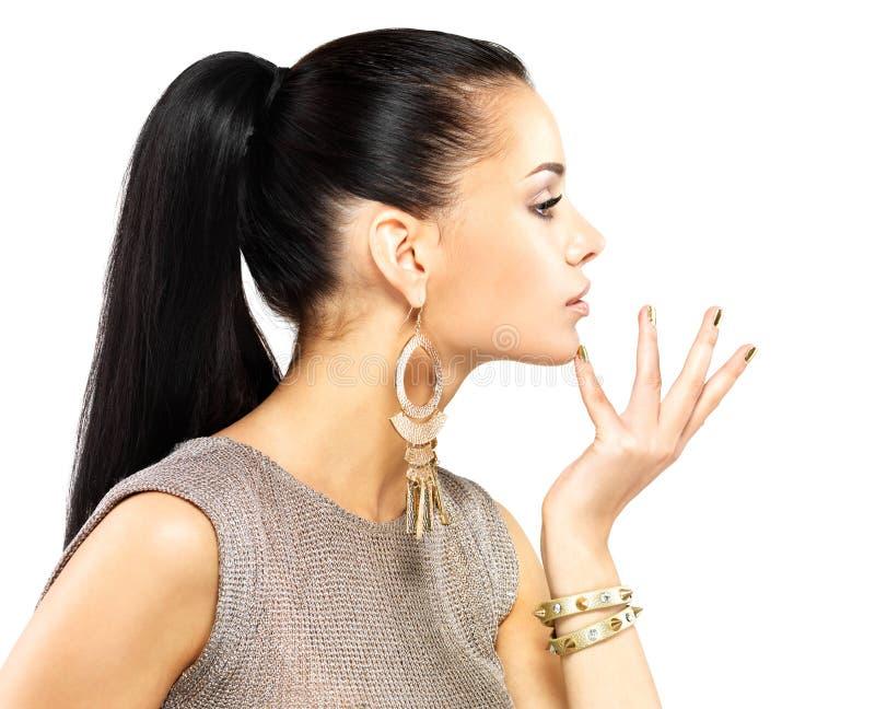 有金黄钉子和美丽的金珠宝的妇女 免版税库存图片