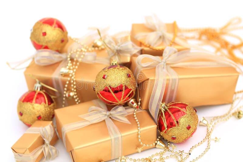 有金黄丝带和chrismas球的金黄礼物盒在白色 免版税库存图片