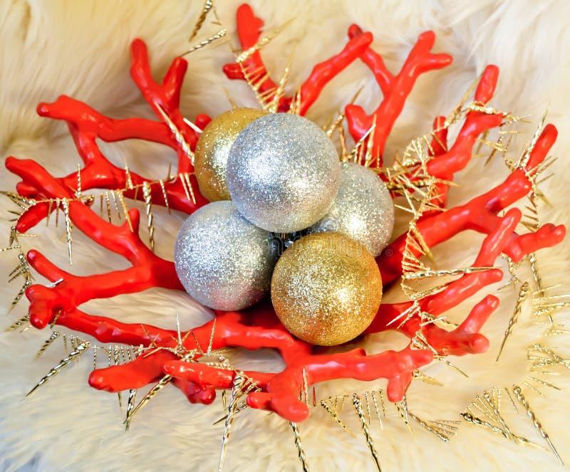 有金黄和银色圣诞节(新年)球的红色有金黄冰柱的花瓶和诗歌选在绵羊毛皮背景 免版税图库摄影