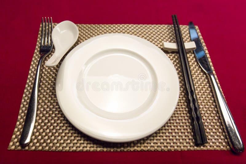 有金黄垫的碗筷投入了红色桌 免版税库存图片
