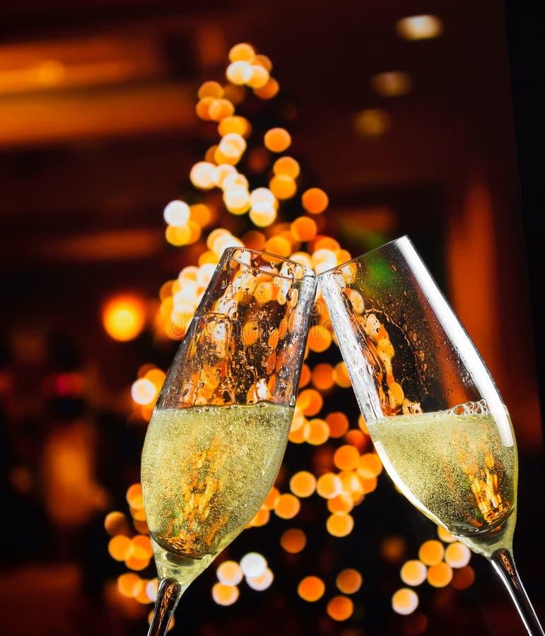 有金黄泡影的香槟槽在圣诞灯装饰背景 免版税库存图片